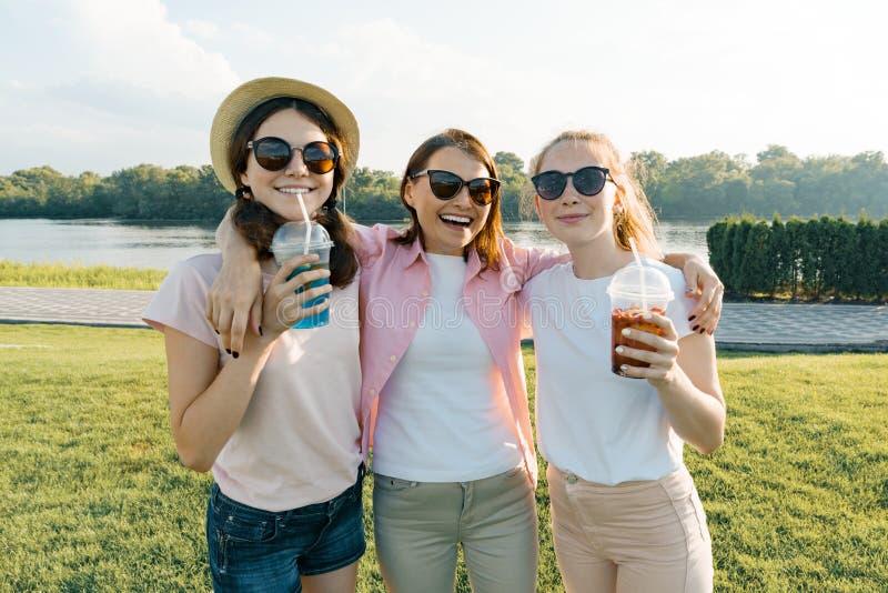 Portret van gelukkige moeder en dochterstieners 14 en 16 jaar oud, meisjes met de zomerdranken Achtergrondaard, recreatiegebied royalty-vrije stock afbeelding