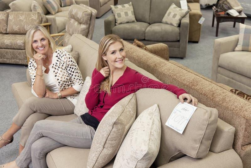 Portret van gelukkige moeder en dochterzitting op bank in meubilairopslag royalty-vrije stock afbeelding