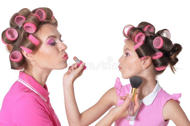 Portret van gelukkige moeder en weinig dochter die make-up op witte achtergrond maken stock foto