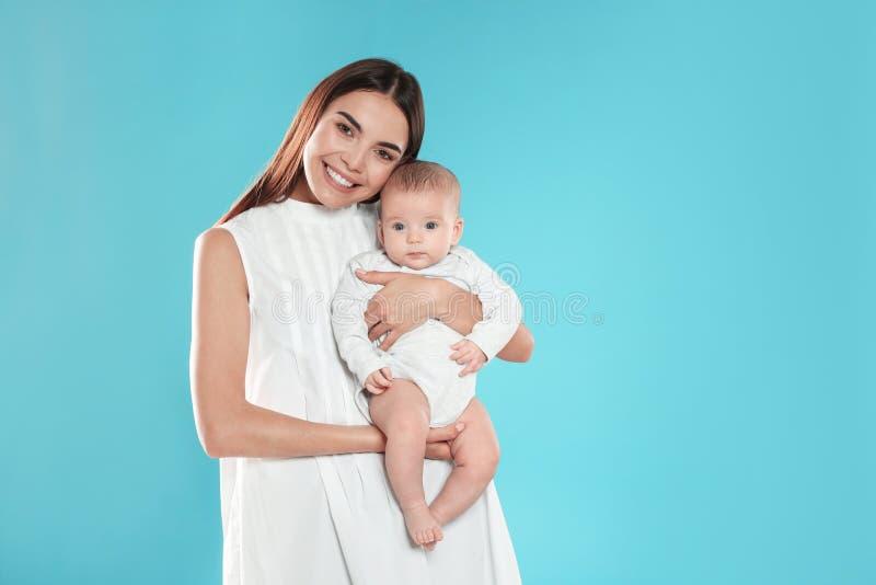 Portret van gelukkige moeder met haar baby op kleurenachtergrond royalty-vrije stock afbeelding