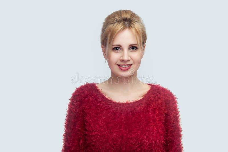 Portret van gelukkige mooie jonge blonde vrouw met make-up en verzameld kapsel in rode blouse die en zich camera bevinden bekijke stock foto's