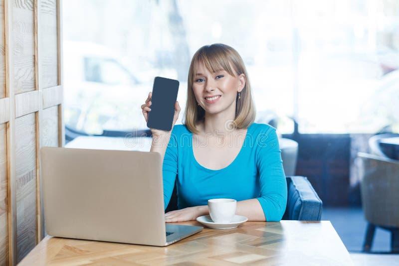 Portret van gelukkige mooie jonge blondevrouw in blauwe t-shirt, zittend met laptop, houdend en tonend mobiele vertoning en royalty-vrije stock fotografie