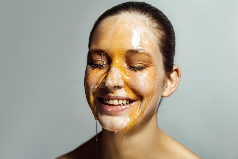 Portret van gelukkige mooie jonge donkerbruine vrouw met sproeten en honing op gezicht met gesloten ogen en toothy gezicht van he stock foto's