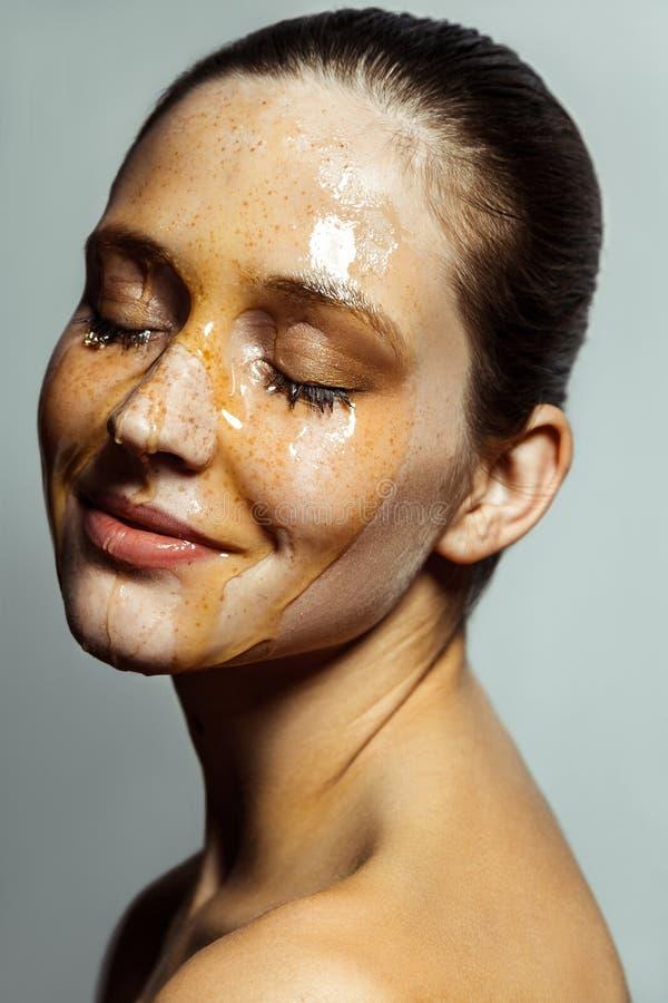Portret van gelukkige mooie jonge donkerbruine vrouw met sproeten en honing op gezicht met het gesloten ogen en gezicht van het g royalty-vrije stock foto