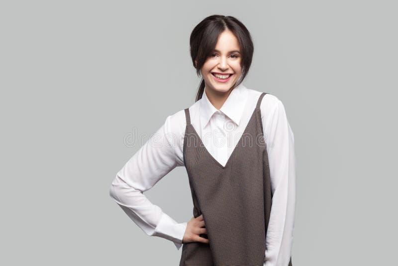 Portret van gelukkige mooie jonge vrouw in wit overhemd en bruine schort met make-up en verzameld haar die en bevinden bekijken z stock afbeelding