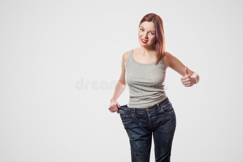 Portret van gelukkige mooie slanke taille van jonge vrouw in grote jea stock foto's