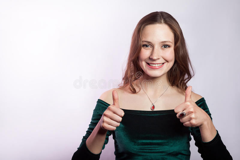 Portret van gelukkige mooie vrouw met sproeten en klassieke groene kleding met omhoog duimen Het schot van de studio stock foto
