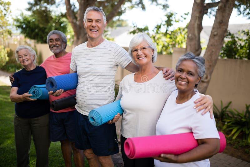 Portret van gelukkige multi-etnische vrienden die oefeningsmatten dragen stock foto