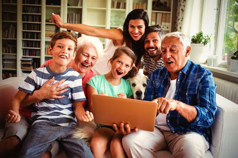 Portret van gelukkige multigeneratie die laptop met behulp van royalty-vrije stock afbeeldingen