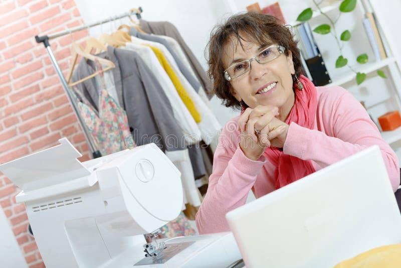 Portret van gelukkige naaistervrouw in studio stock afbeeldingen