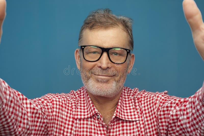 Portret van Gelukkige positieve mensengepensioneerde die rood overhemd en modieuze oogglazen dragen royalty-vrije stock fotografie