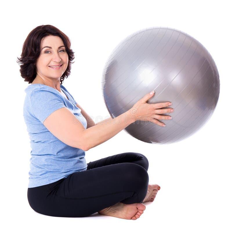 Portret van gelukkige rijpe vrouw die oefeningen met geschiktheidsbal doen stock afbeeldingen