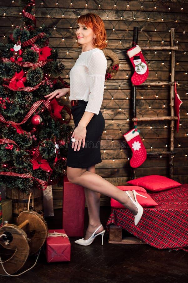 Portret van gelukkige rode haired vrouw dichtbij Kerstmisboom stock foto's
