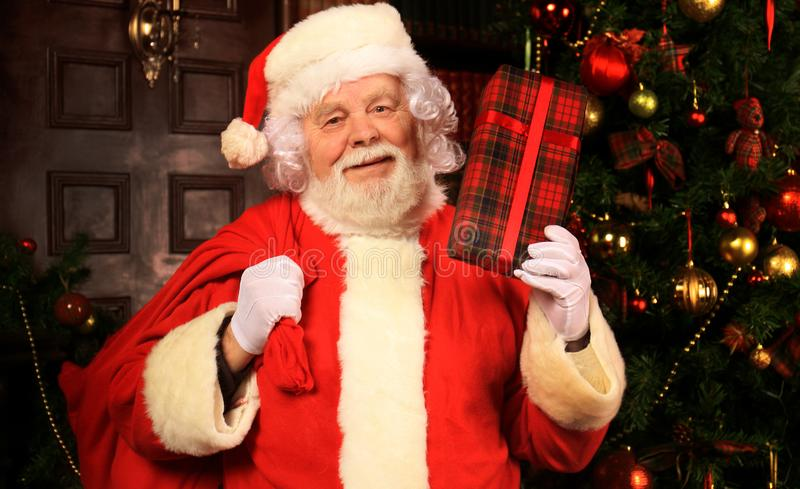 Portret van gelukkige Santa Claus bij zijn ruimte thuis dichtbij Kerstboom met giftdoos stock foto's