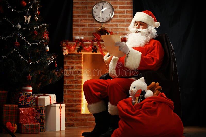 Portret van gelukkige Santa Claus-zitting bij zijn ruimte thuis stock afbeeldingen