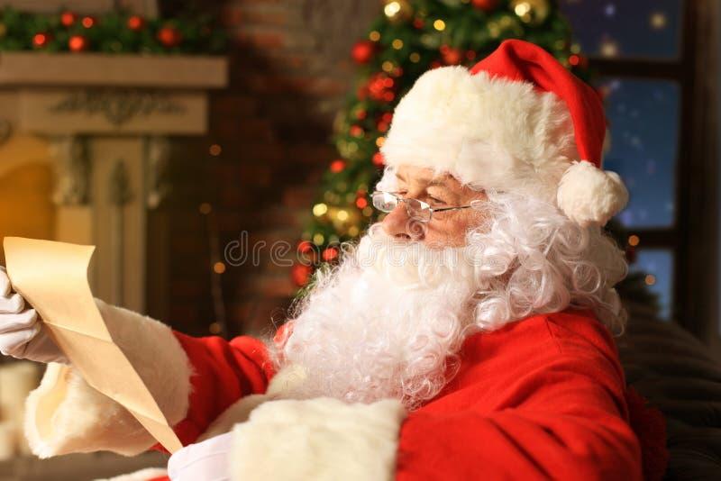 Portret van gelukkige Santa Claus-zitting bij zijn ruimte thuis dichtbij Kerstboom en de brief van lezingskerstmis of wenslijst stock foto's