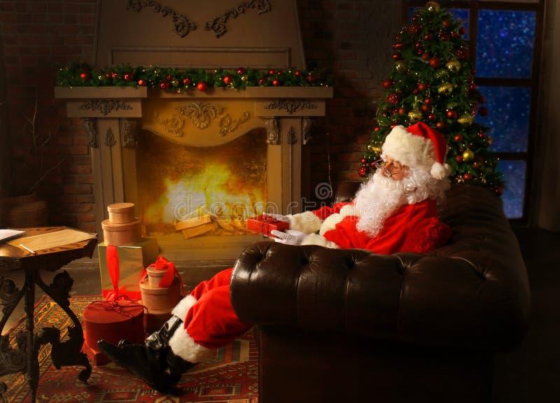 Portret van gelukkige Santa Claus-zitting bij zijn ruimte thuis dichtbij Kerstboom en de brief van lezingskerstmis of wenslijst royalty-vrije stock foto