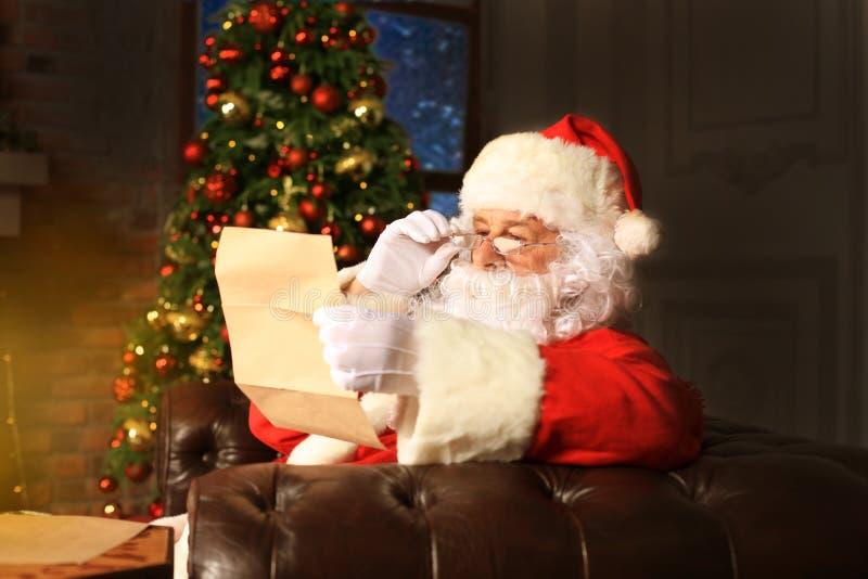 Portret van gelukkige Santa Claus-zitting bij zijn ruimte thuis dichtbij Kerstboom en de brief van lezingskerstmis of wenslijst stock foto