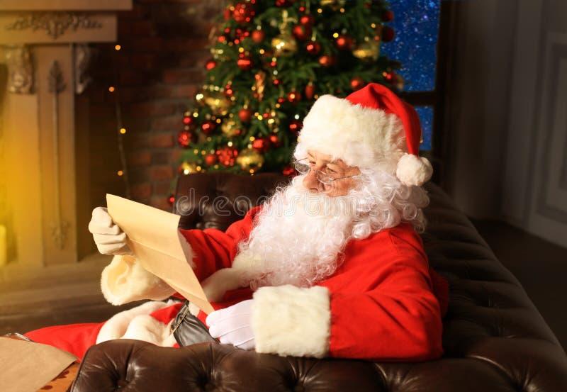 Portret van gelukkige Santa Claus-zitting bij zijn ruimte thuis dichtbij Kerstboom en de brief van lezingskerstmis of wenslijst stock afbeelding