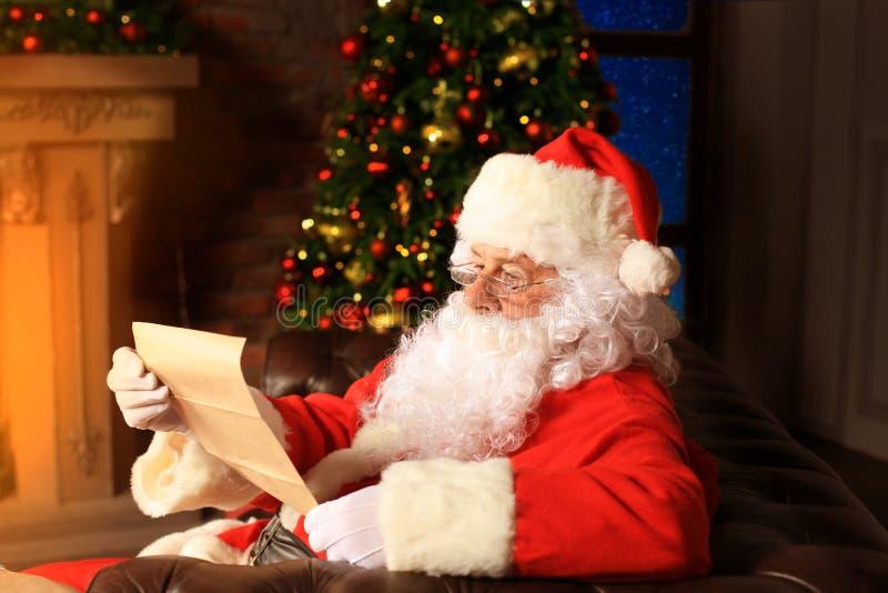 Portret van gelukkige Santa Claus-zitting bij zijn ruimte thuis dichtbij Kerstboom en de brief van lezingskerstmis of wenslijst royalty-vrije stock fotografie