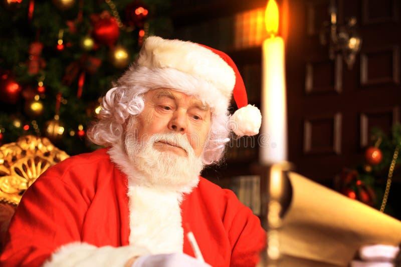 Portret van gelukkige Santa Claus-zitting bij zijn ruimte thuis dichtbij Kerstboom en de brief van lezingskerstmis of wenslijst royalty-vrije stock afbeeldingen