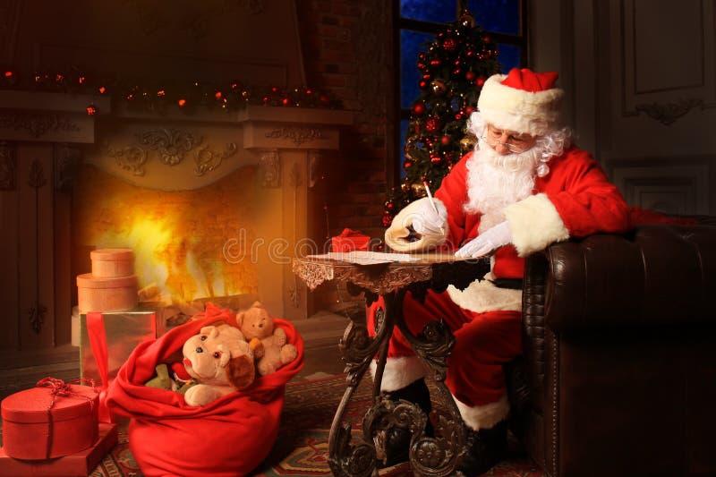 Portret van gelukkige Santa Claus-zitting bij zijn ruimte thuis dichtbij Kerstboom en het beantwoorden van Kerstmisbrieven stock foto
