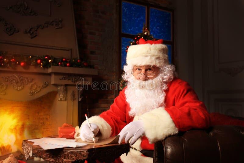 Portret van gelukkige Santa Claus-zitting bij zijn ruimte thuis dichtbij Kerstboom en het beantwoorden van Kerstmisbrieven royalty-vrije stock afbeeldingen