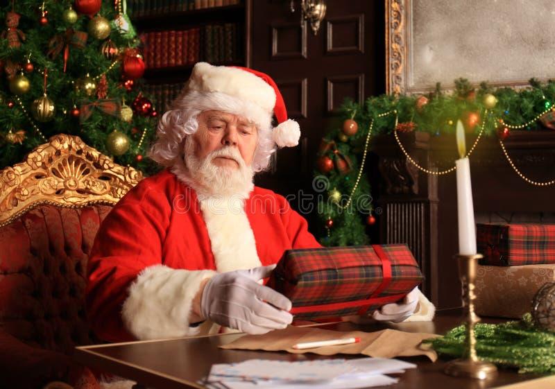 Portret van gelukkige Santa Claus-zitting bij zijn ruimte thuis dichtbij Kerstboom met giftdoos stock foto