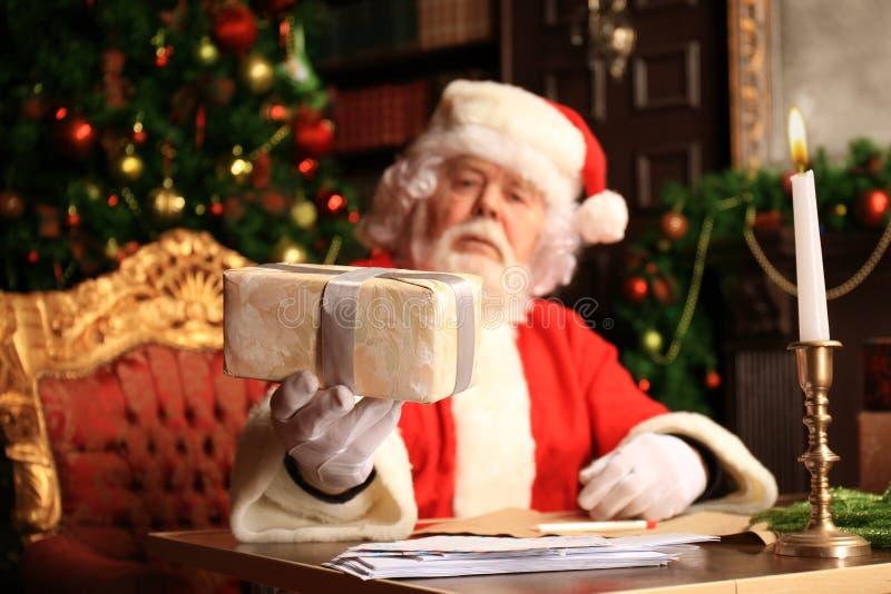 Portret van gelukkige Santa Claus-zitting bij zijn ruimte thuis dichtbij Kerstboom met giftdoos royalty-vrije stock foto's