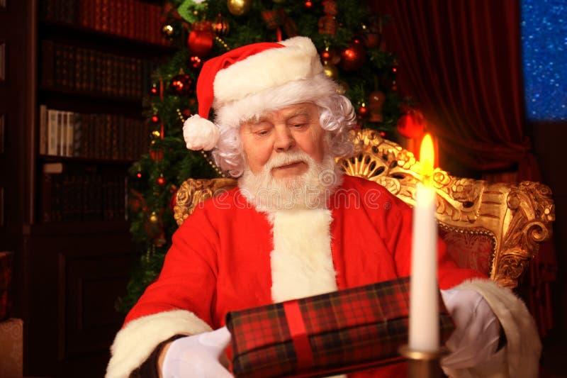 Portret van gelukkige Santa Claus-zitting bij zijn ruimte thuis dichtbij Kerstboom met giftdoos stock foto's