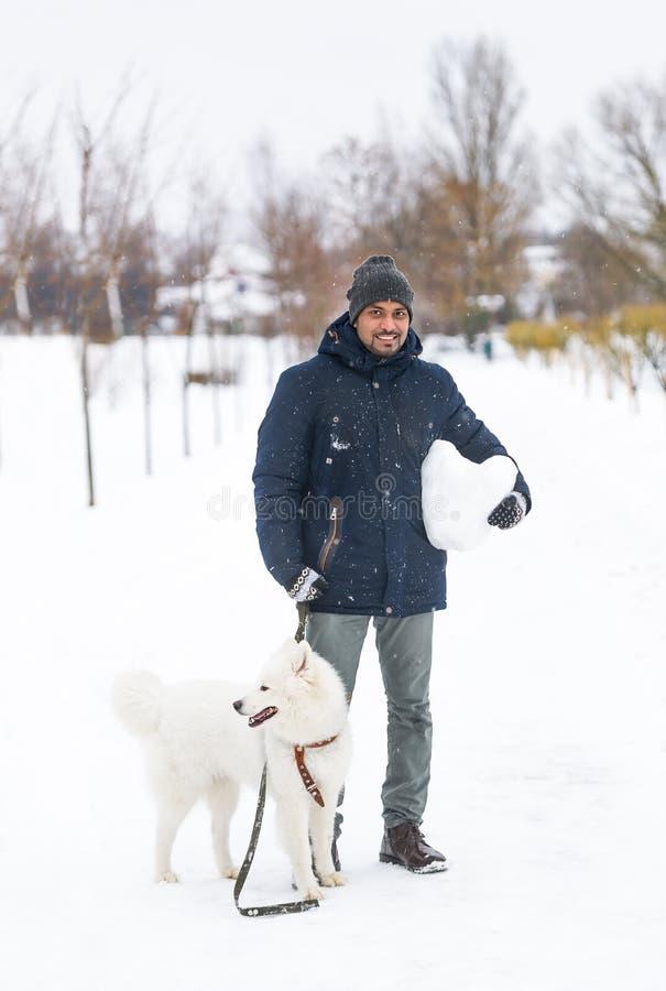 Portret van gelukkige sri lankan met witte Samoyed-hond in openlucht op de sneeuw in de winterdag royalty-vrije stock foto