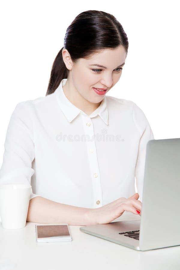 Portret van gelukkige succesvolle aantrekkelijke donkerbruine onderneemster die in witte overhemdszitting met laptop, vertoning b stock afbeeldingen