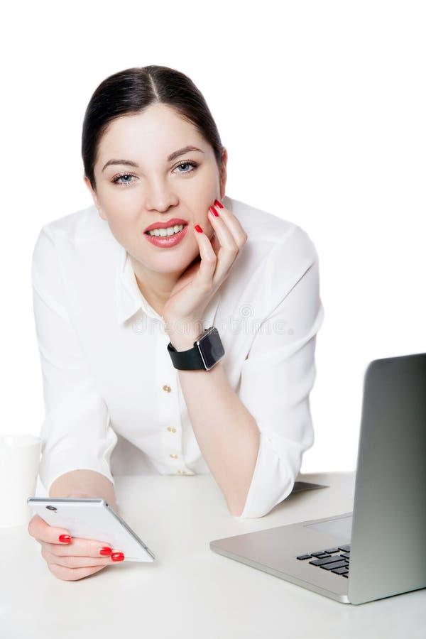 Portret van gelukkige succesvolle aantrekkelijke donkerbruine onderneemster in witte overhemdszitting, holding haar mobiele smart stock foto