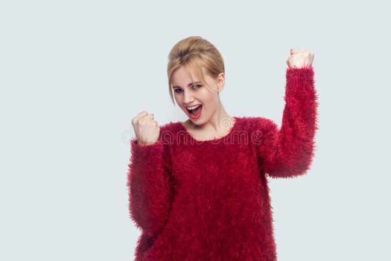 Portret van gelukkige succesvolle verheugende mooie jonge blonde vrouw in rode blouse die, en haar overwinning bevinden zich vier stock fotografie