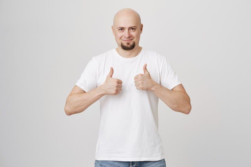 Portret van gelukkige tevreden kale gebaarde duimen tonen en kerel die, zijnd tevreden met punt dat hij, status heeft gekocht gli stock foto's