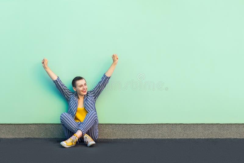 Portret van gelukkige verheugende knappe mooie korte haar jonge vrouw in toevallig gestreept kostuum die en haar overwinning zitt stock foto