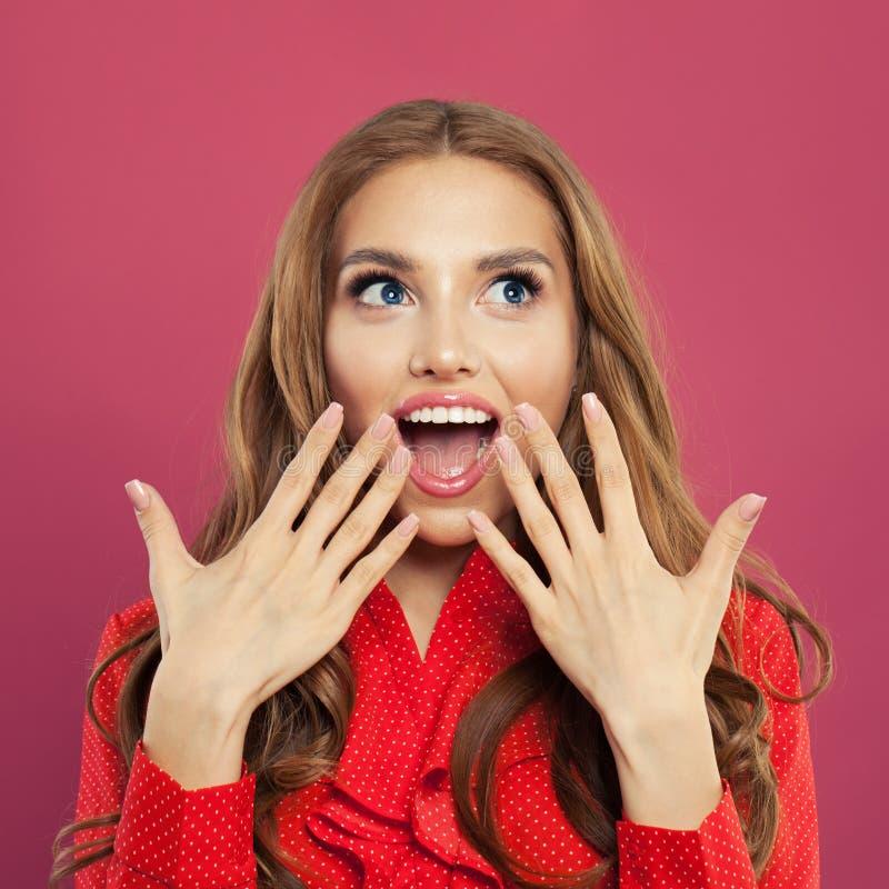 Portret van gelukkige verraste vrouw op kleurrijke heldere roze achtergrond Studioschot van het vrij opgewekte krullende meisje v royalty-vrije stock fotografie