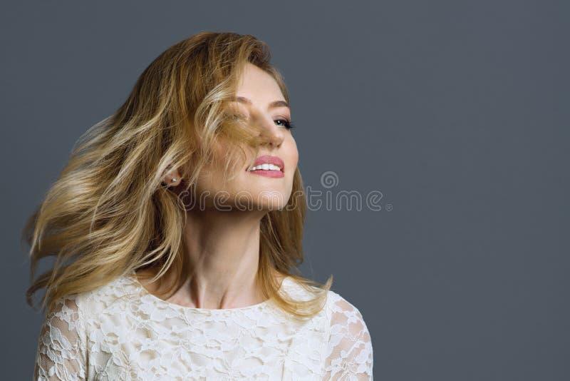Portret van gelukkige volwassen blondevrouw die haar hoofd, grijze achtergrond spinnen royalty-vrije stock fotografie