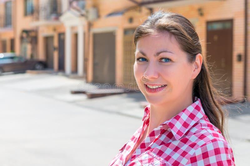 Portret van gelukkige vrouw dichtbij haar nieuw huis stock afbeelding