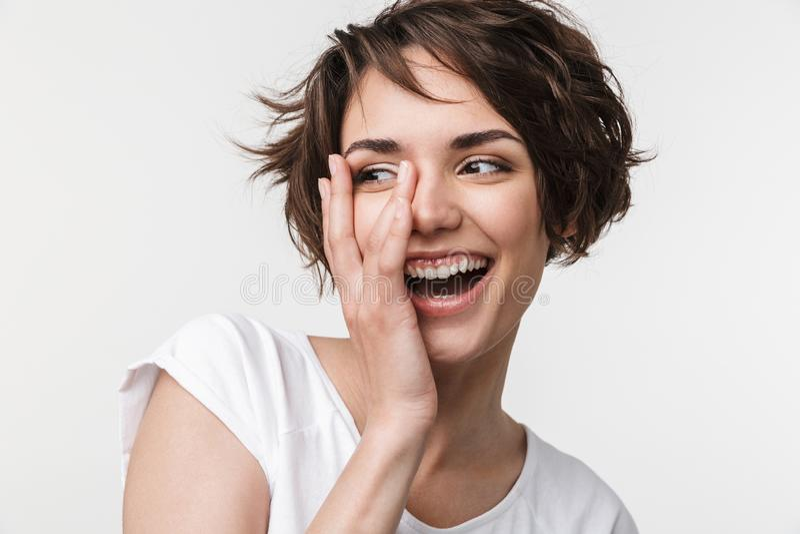 Portret van gelukkige vrouw met kort bruin haar in basist-shirt die en wat betreft haar gezicht met hand glimlachen stock afbeeldingen