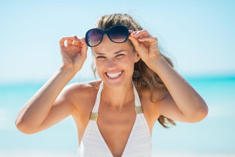 Portret van gelukkige vrouw met oogglazen op strand stock fotografie