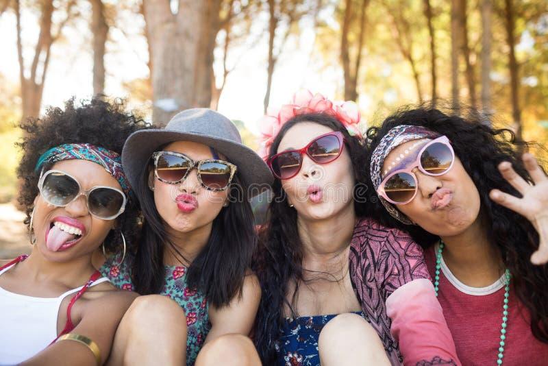 Portret van gelukkige vrouwelijke vrienden die gezichten maken bij kampeerterrein stock afbeeldingen