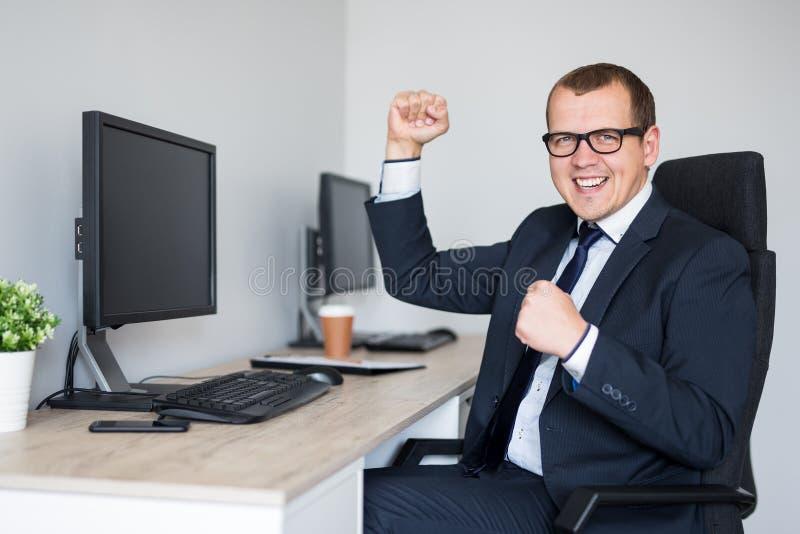 Portret van gelukkige zakenman die iets in modern bureau vieren stock afbeelding