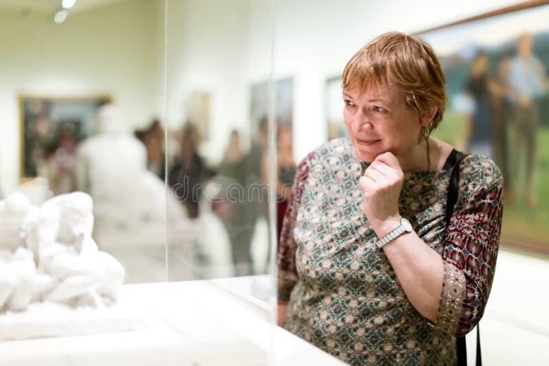 Portret van gepensioneerdenvrouw die aandachtig beeldhouwwerken bekijken stock foto's