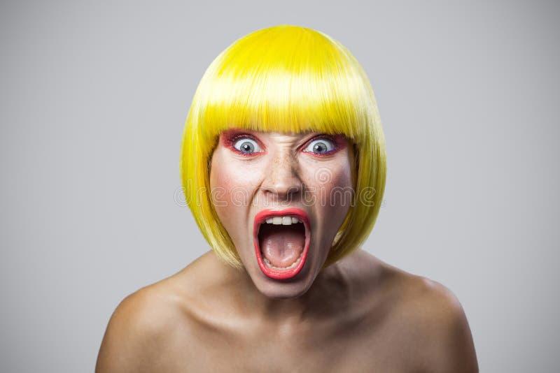 Portret van geschokte jonge vrouw die met sproeten, rode make-up en gele pruik camera met ongelooflijk gezicht en het gillen beki royalty-vrije stock fotografie