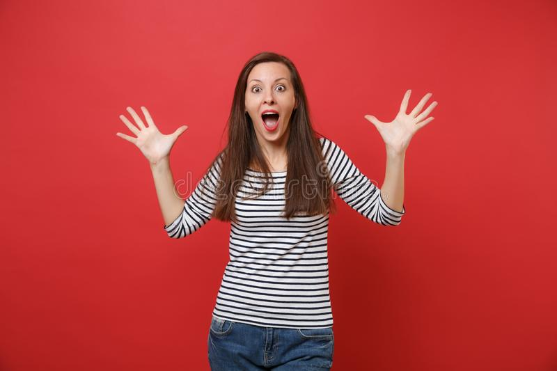 Portret van geschokte jonge vrouw mond brede open, kijkend verrast en het uitspreiden handen die op helder rood geïsoleerd houden royalty-vrije stock foto