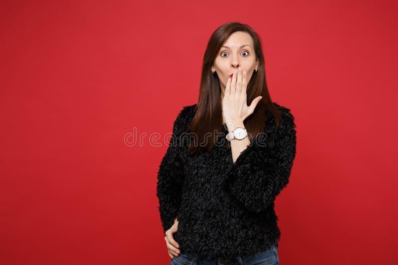 Portret van geschokte verbaasde jonge vrouw in zwarte bontsweater die mond behandelen die met palm op heldere rode muur wordt geï royalty-vrije stock afbeelding