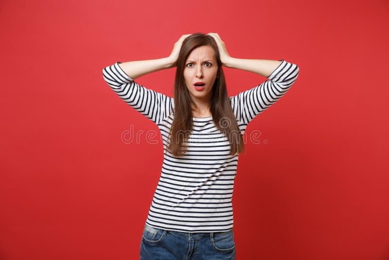 Portret van geschokte verwarde jonge vrouw in gestreepte kleren die die en handen op hoofd bevinden zetten op helder rood wordt g royalty-vrije stock foto