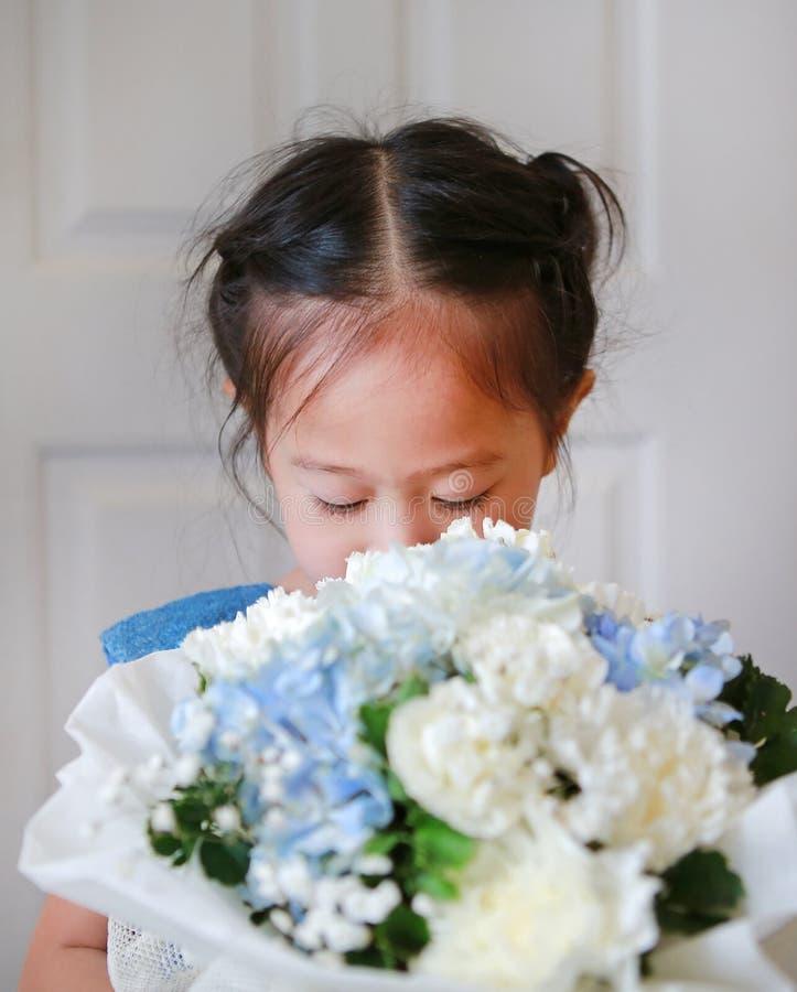 Portret van gesloten leuke ogen weinig kindmeisje met Boeket van rozen stock foto