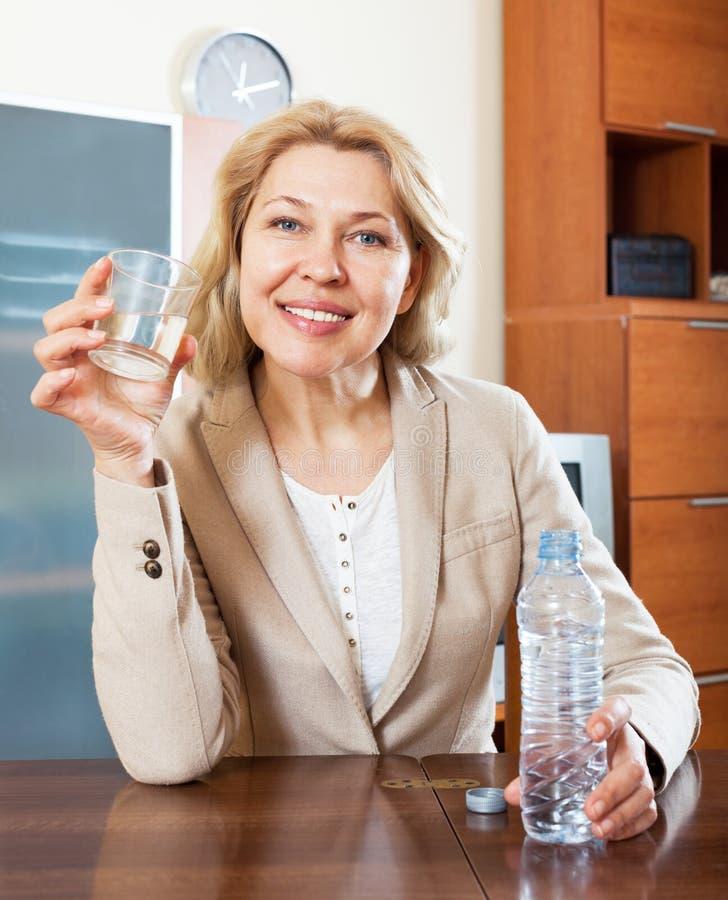 Portret van gewone vrouw met schoon water bij lijst stock afbeelding